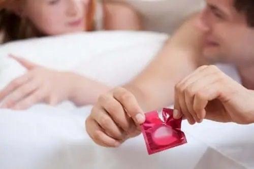 Bărbat care desface un prezervativ lângă parteneră