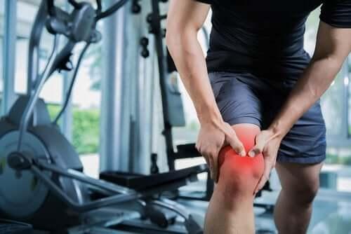 Bărbat experimentând o durere de genunchi la sală