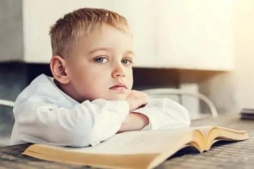 Copil care stă cu capul pe o carte