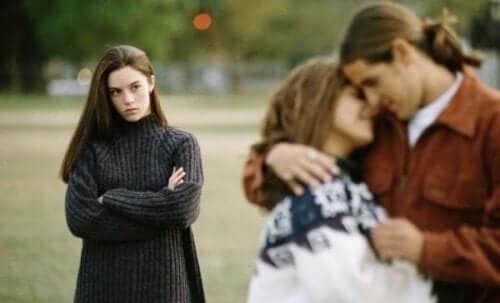 Femeie privind un cuplu cu gelozie