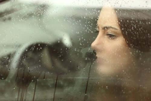 Femeie privind printr-un geam udat de ploaie