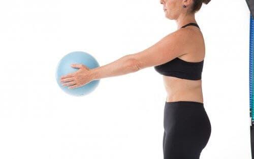 Femeie antrenându-se cu o minge de cauciuc