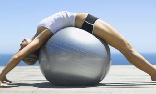 Femeie întinzându-și spatele pe o minge uriașă