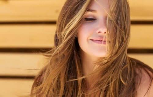 Femeie zâmbind pentru că a aplicat trucuri pentru prevenirea căderii părului