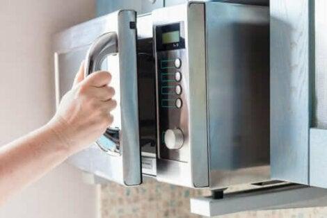 Gospodină deschizând ușa unui cuptor cu microunde