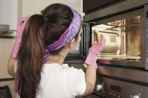 Gospodină aplicând metode de curățare a cuptorului