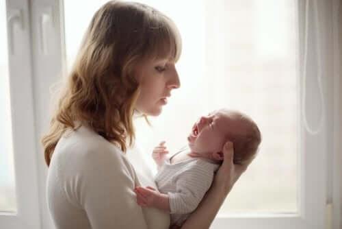 Mămică încercând trucuri pentru eliminarea gazelor intestinale la bebeluși