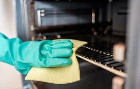 Mână curățând interiorul unui cuptor cu o cârpă