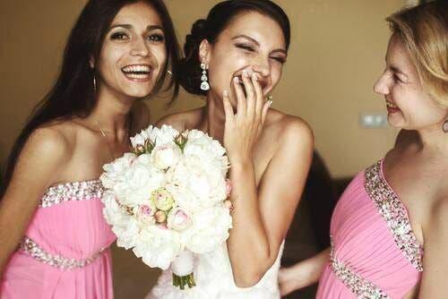 Mireasă râzând împreună cu domnișoarele sale de onoare
