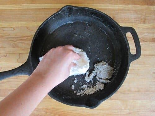 Persoană curățând o tigaie cu un detergent natural