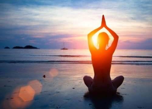Persoană practicând yoga pe plajă pentru a avea o sănătate mintală optimă