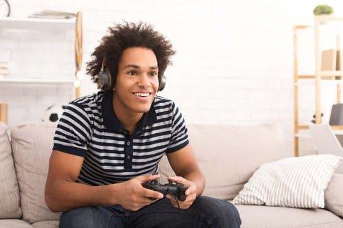 Băiat stând pe canapea și jucându-se un joc video pe consolă
