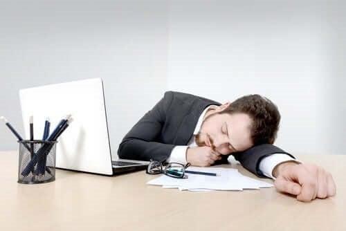 Bărbat care doarme cu capul pe birou