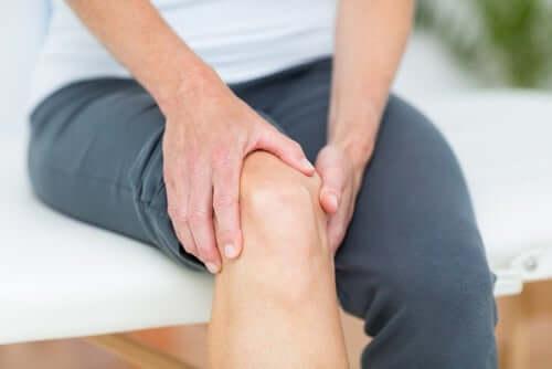 Barbat experimentând o durere de genunchi