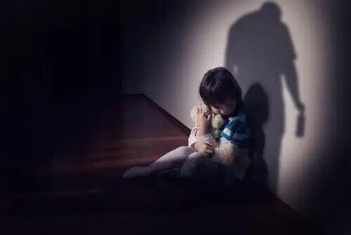 Copil speriat cu jucărie în brațe