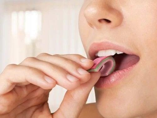 Fată care bagă în gură gumă de mestecat