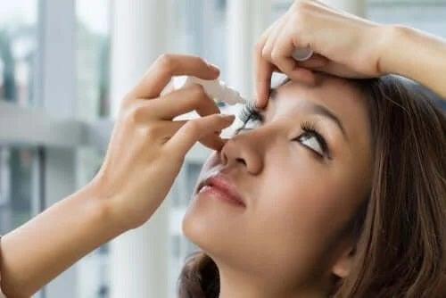 Fată care își pune în ochi soluția oftalmică cu oximetazolină