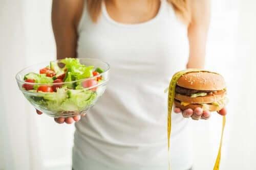 Femeie ținând în mână alimente pentru prevenirea obezității și un burger