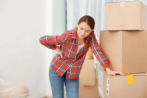 Femeie experimentând o durere de spate în timpul mutării
