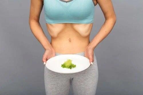 Femeie care ține o farfurie cu o frunză de salată