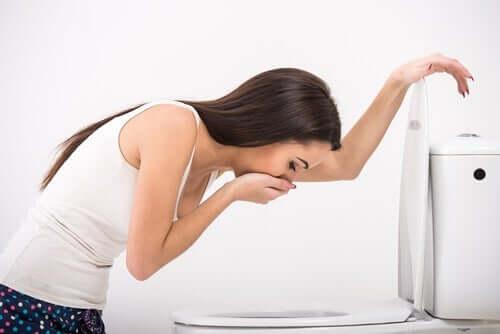 Femeie experimentând greață în baie