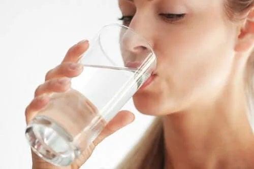 Femeie care se hidratează bând apă