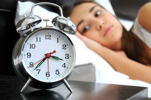 Femeie cu insomnie privind ceasul de pe noptieră