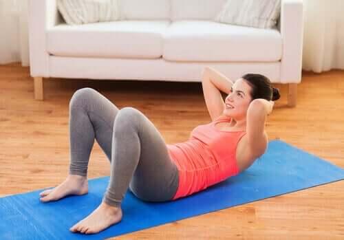Femeie antrenându-și mușchii abdominali acasă