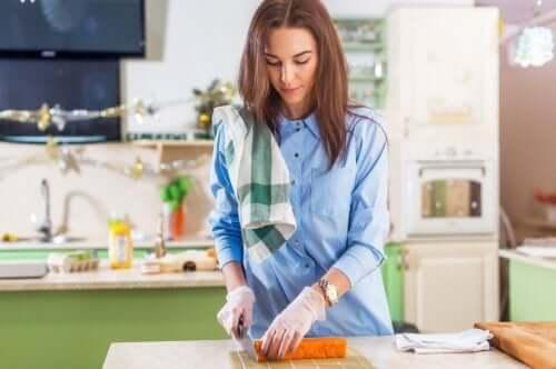 Femeie tăind legume cu mănuși în mâini