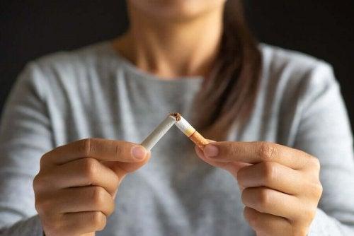 Femeie rupând o țigară în două