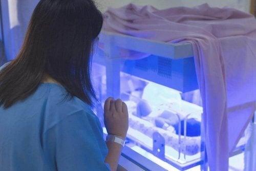 Mămică privind un aparat folosit pentru a trata icterul la nou-născuți