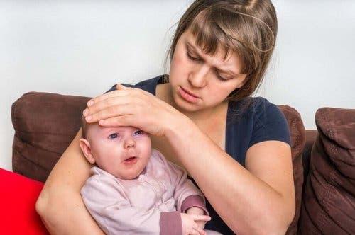 Mămică luând temperatura bebelușului său