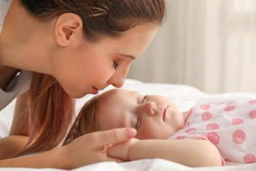 Mămică aplicând un tratament pentru plagiocefalie bebelușului său
