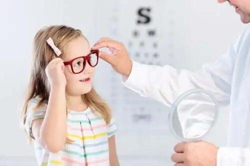 Medic care îi pune ochelari unei fetițe