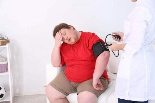 Medic luând tensiunea unui pacient obez