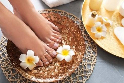 Picioare înmuiate într-un castron cu apă și flori