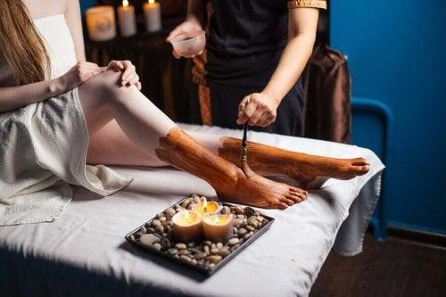 Specialist aplicând argilă pe picioarele unei cliente