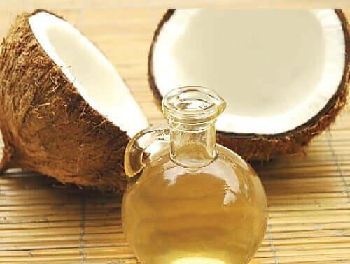 Sticlă cu ulei lângă o nucă de cocos ruptă în două