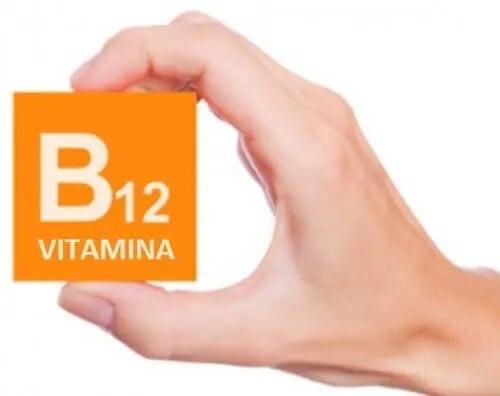 Mână care ține un cub pe care scrie vitamina B12