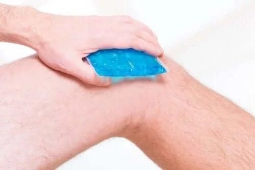 Bărbat care își pune gheață pe genunchi