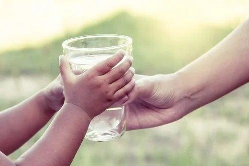 Copil care primește un pahar cu apă