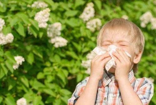 Copil care își suflă nasul