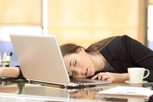 Fată care doarme cu capul pe laptop