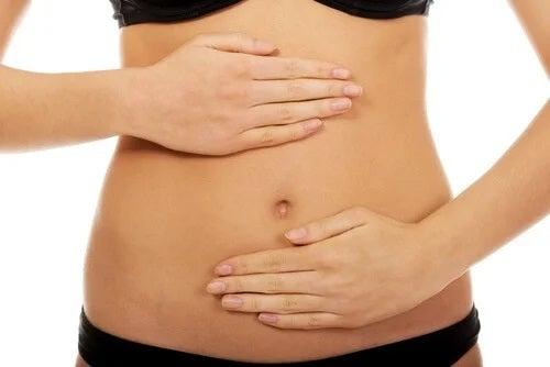 Femeie cu mâinile pe abdomen