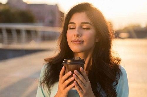 Femeie care bea cafea în oraș