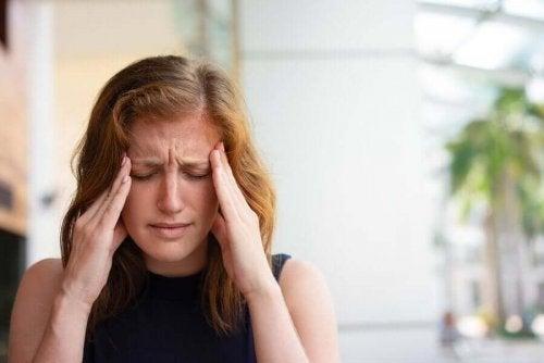 Femeie experimentând o durere de cap intensă