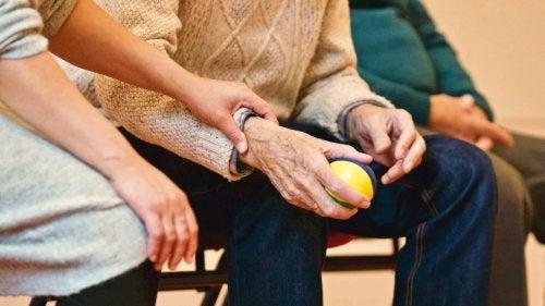 Femeie ținând mâna unui pacient cu boala Parkinson