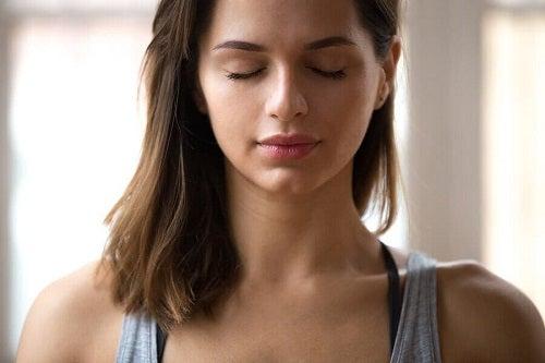 Femeie meditând pentru îmbunătățirea sănătății emoționale