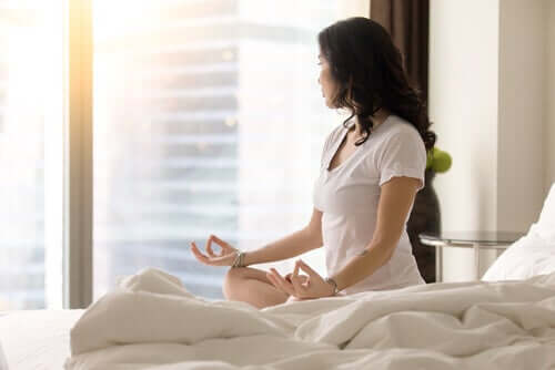 Femeie meditând în pat