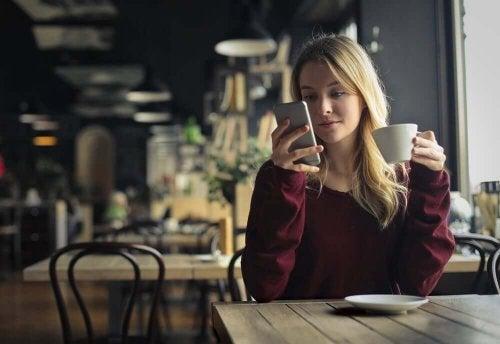 Femeie verificându-și telefonul mobil la cafenea